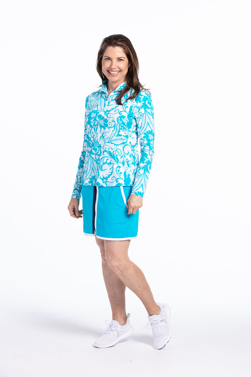 women standing wearing a longsleeve bright blue floral golf top and matching solid blue golf skort.