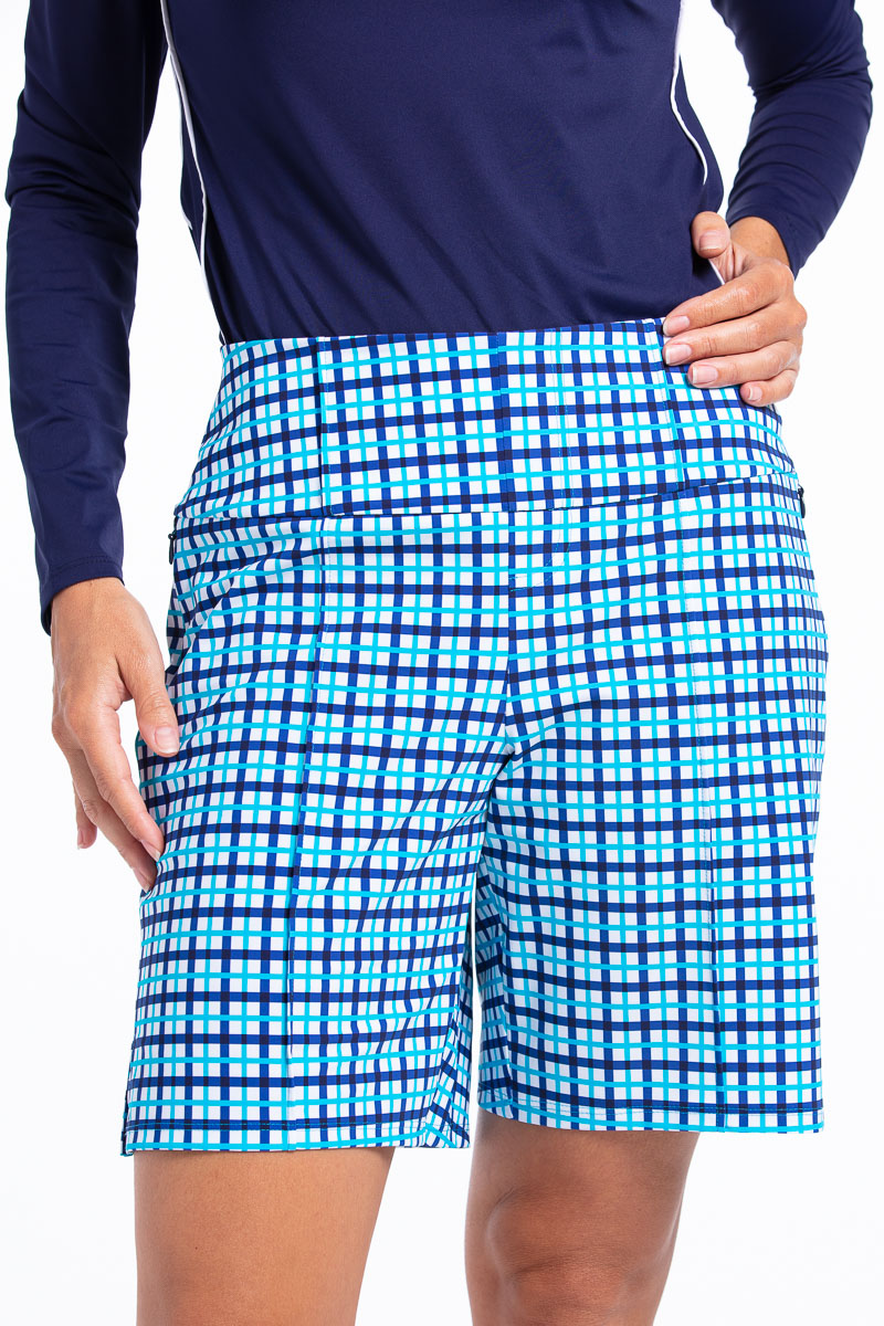women wearing blue check golf short with hand on hip.