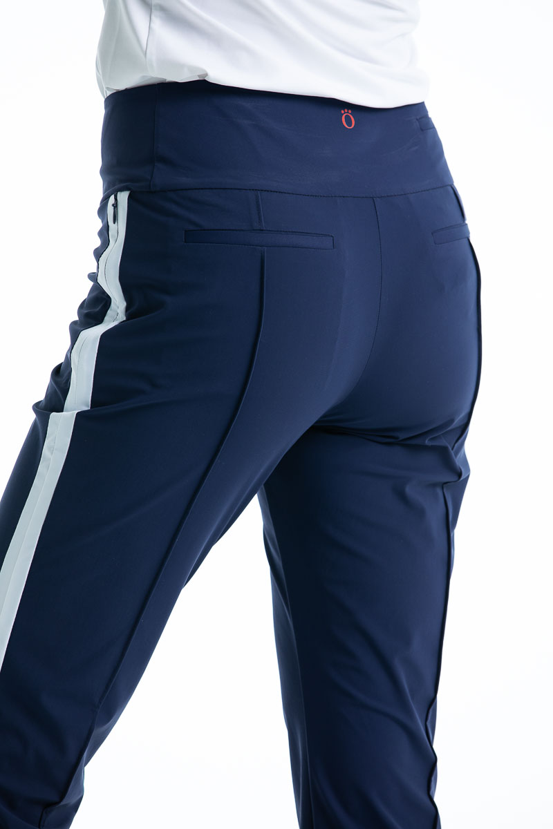 Back view of woman in navy blue Tailored Track golf pant with white trim down the side of the leg.