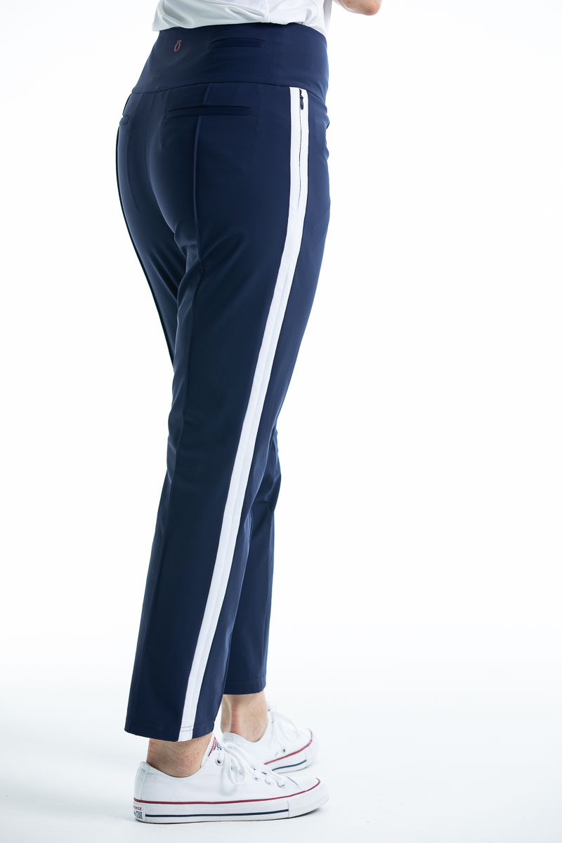 Side view of woman in navy blue Tailored Track  golf pant with white trim down the side of the leg.