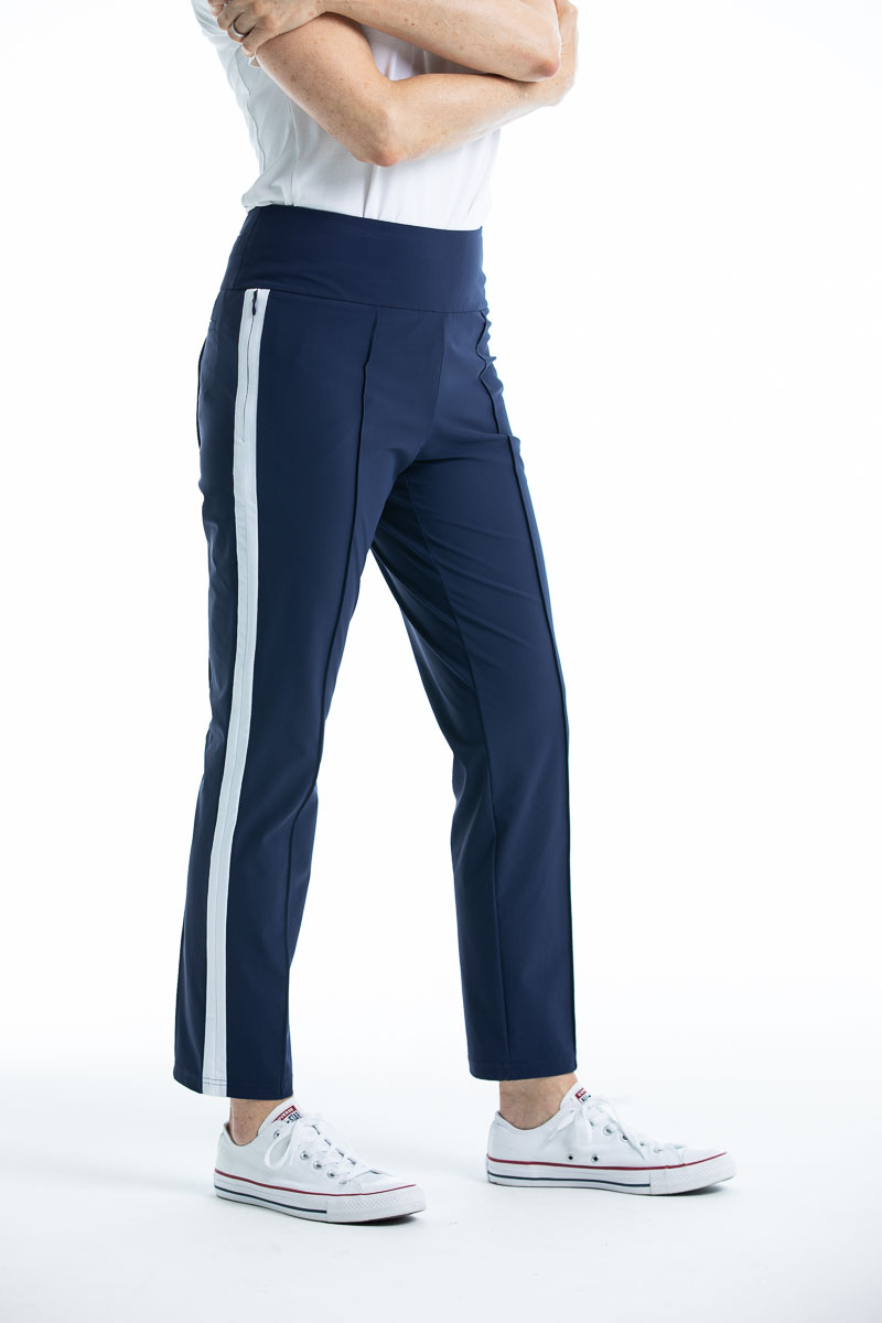 Side view of woman in navy blue Tailored Trim golf pant with white trim down the side of the leg.