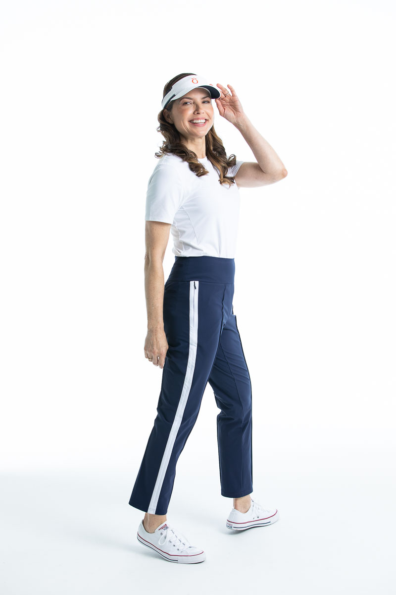 Woman holding the brim of her white No Hat Hair visor wearing a white Tee it Up shortsleeve golf shirt and navy blue Tailored Track golf pant.