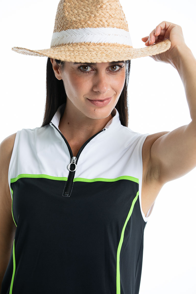 women in black and white golf dress holding brim of straw hat