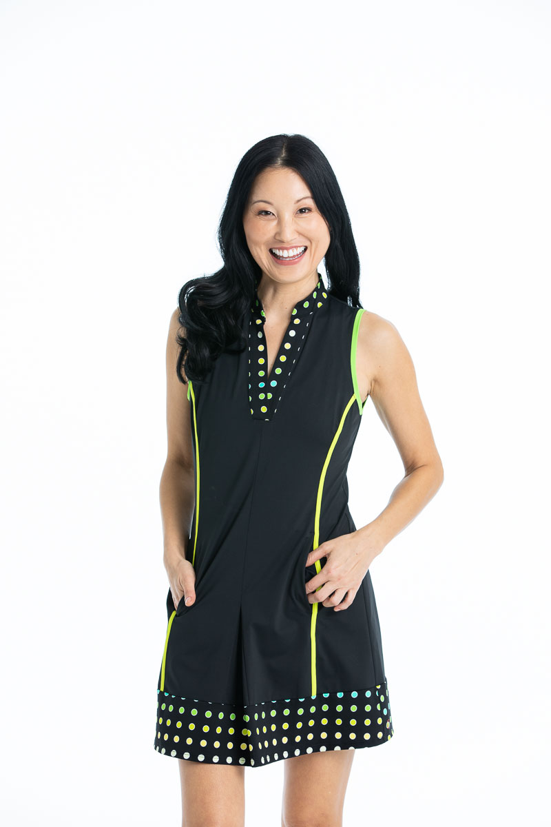 women smiling with hands in pockets wearing black sleeveless golf dress