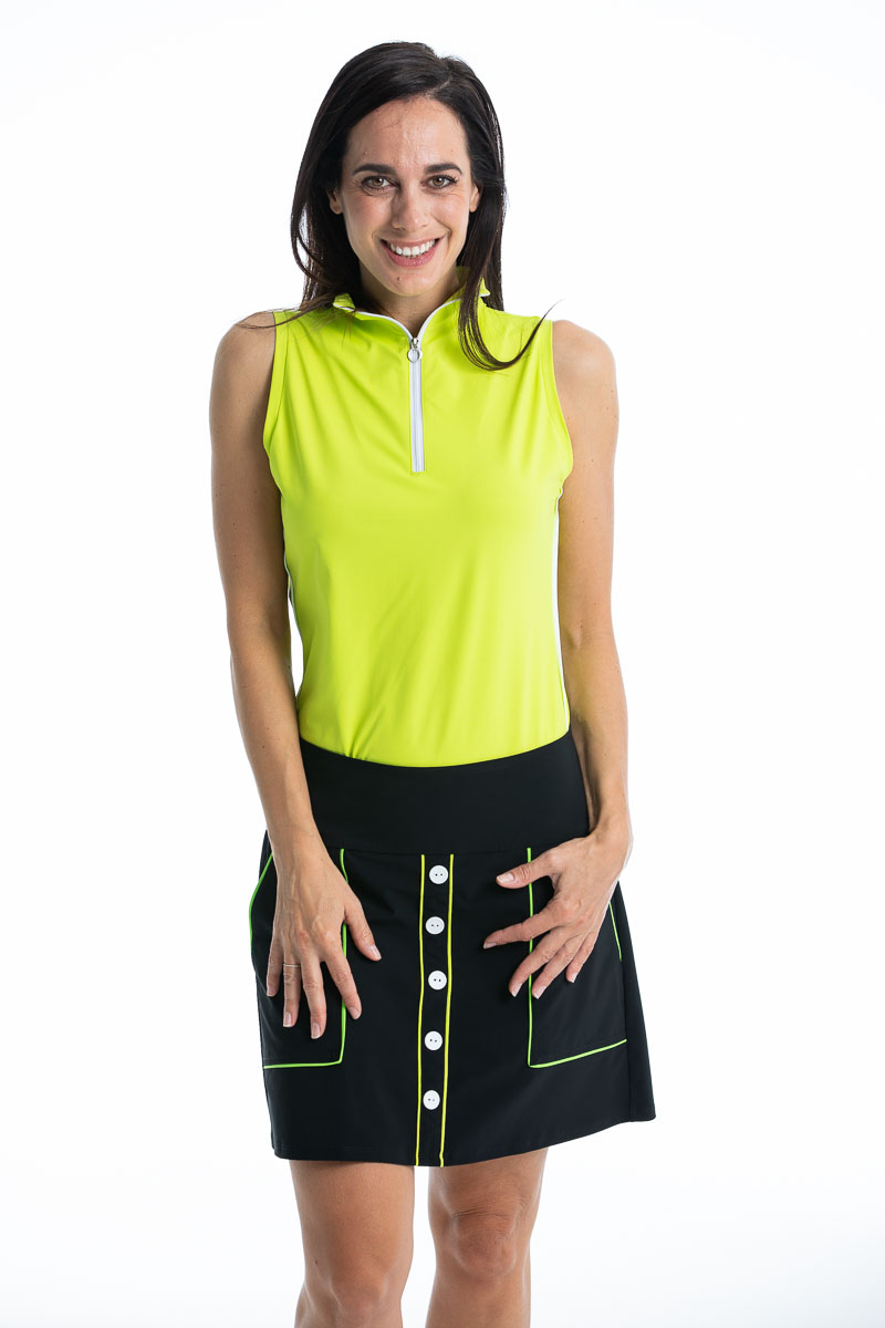 women golfer wearing chartreuse yellow top and black golf skort
