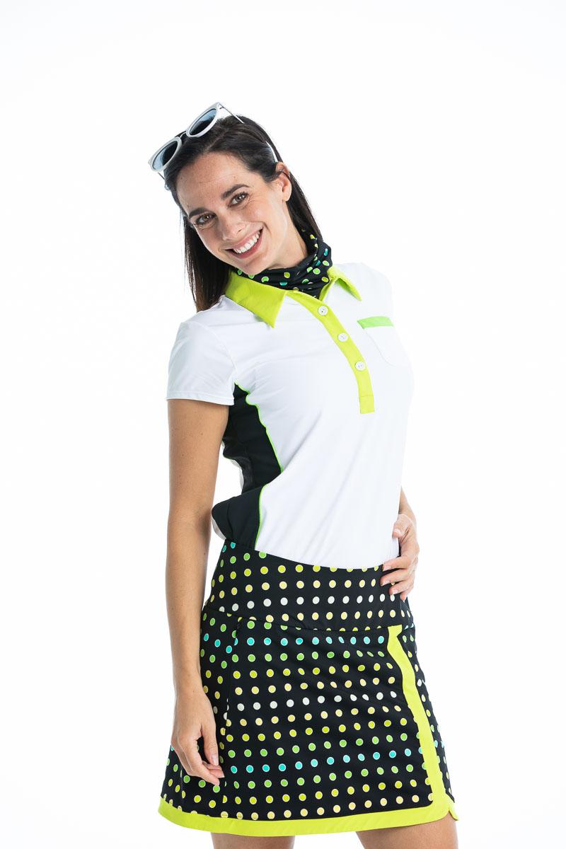 women golfer smiling wearing white shortsleeve golf shirt and polka dot golf skort