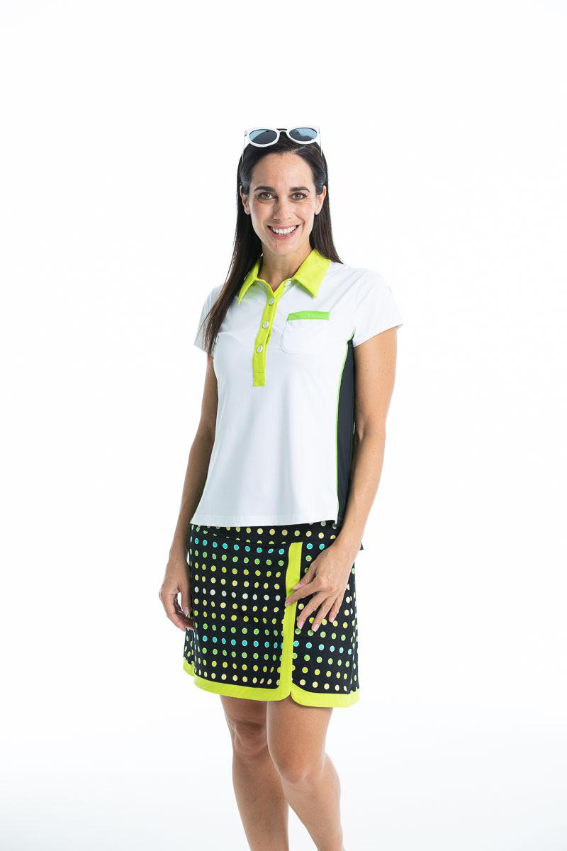 women golfer wearing white shortsleeve golf polo and polka dot skort