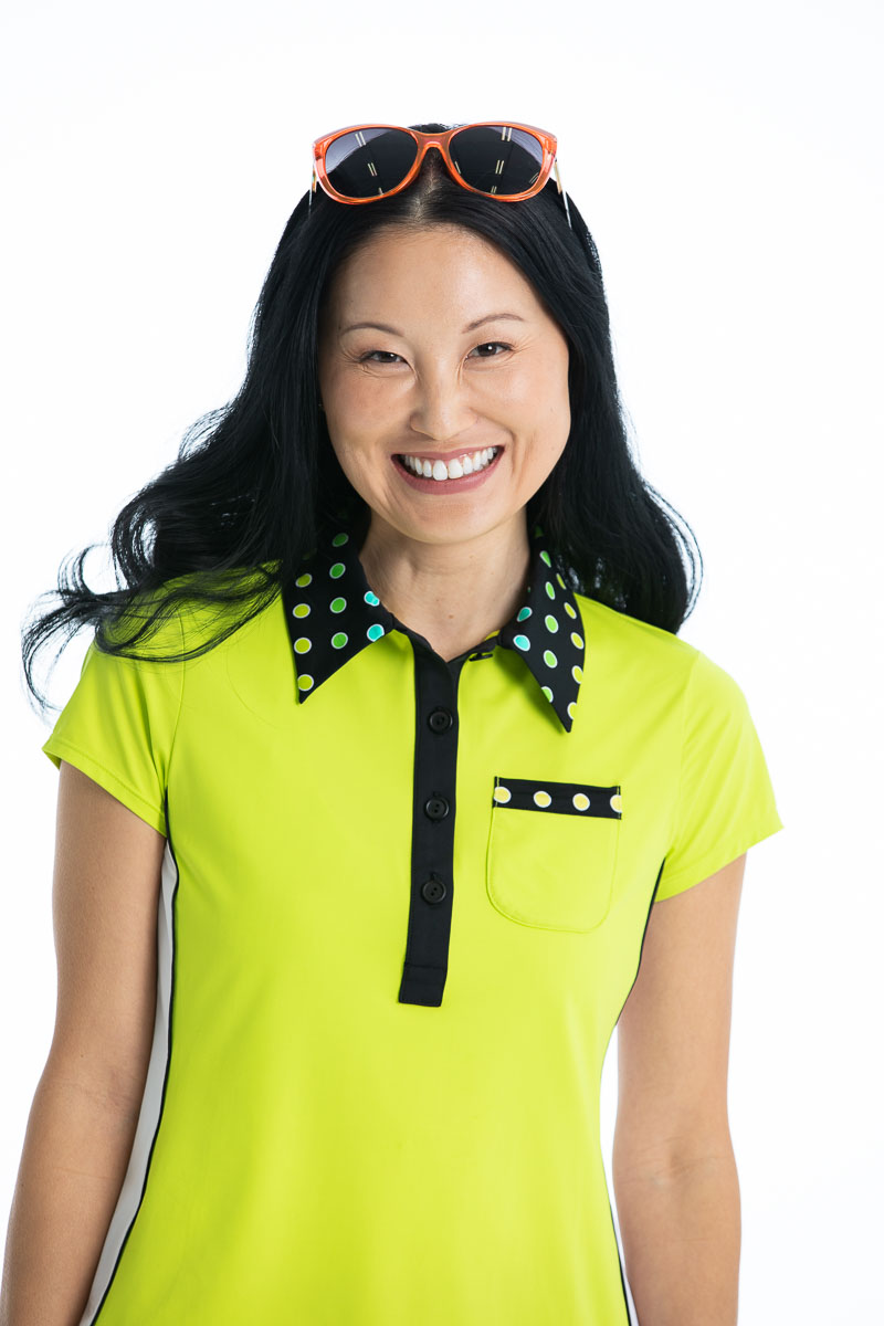 women smiling wearing a charetreuse yellow shortsleeve golf top.