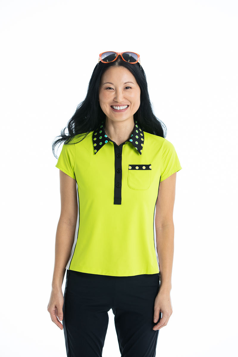 women smiling and wearing a chartreuse yellow shortsleeve golf top and black pants