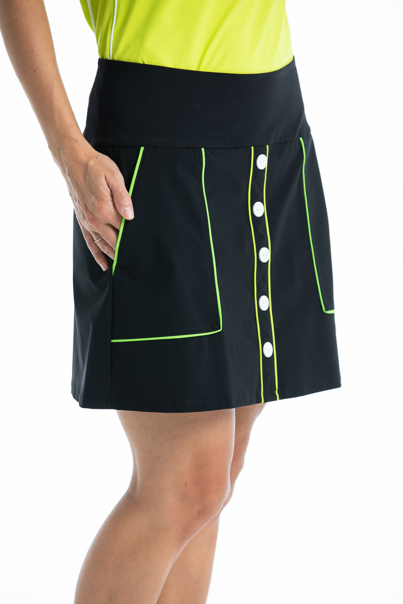 women golfer weraring black golf skort with white buttons and hand in pocket
