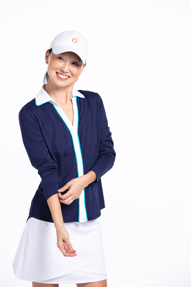 women golfer wearing navy longsleeve golf shirt and white golf skort pushing up her sleeves.