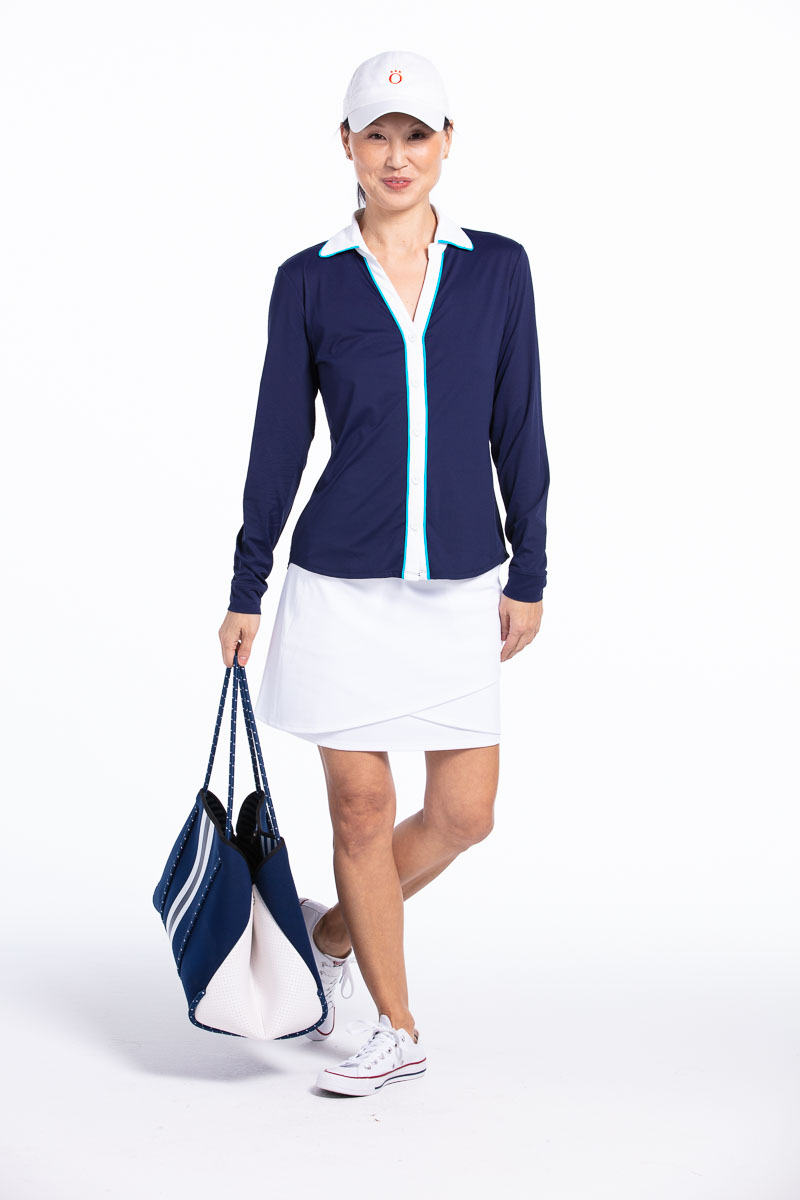 women golfer wearing navy longsleeve golf shirt with white golf skort and golf hat and carrying a navy bag.
