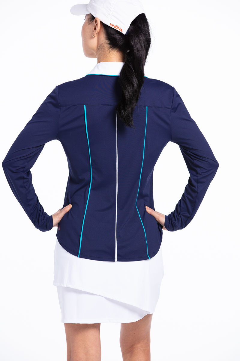 women golfer back view showing back of her navy blue golf shirt and white golf skort with hands on her hips.