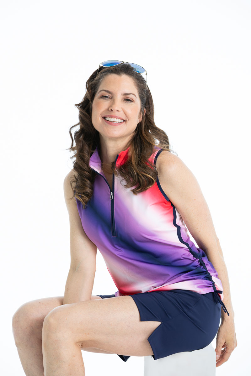 Woman smiling wearing Rouched and Ready sleeveless golf top in ombre print - red, white, and blue