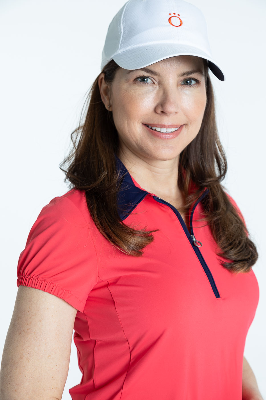 Closer view of woman in a watermelon red shortsleeve Prettier Than a Polo shirt and a white We've Got You Covered hat