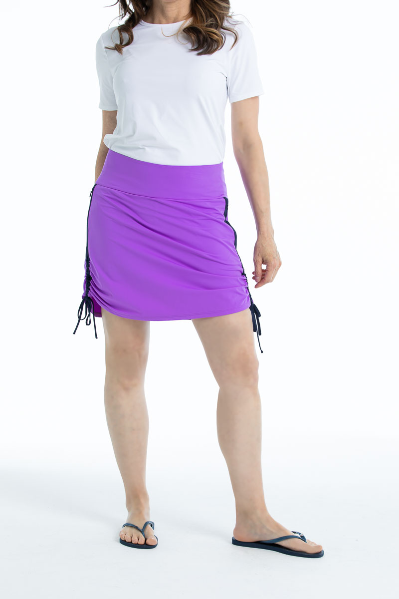 Woman in Rouched and Ready golf skort - lilac purple and a white shortsleeve To a Tee t-shirt