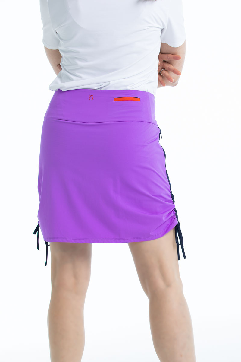 Back view of woman in Rouched and Ready golf skort - lilac purple and a white shortsleeve To a Tee t-shirt