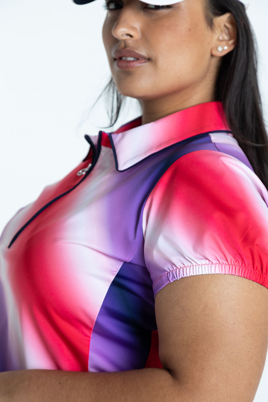 Close up of woman golfer wearing an ombre shortsleeve Prettier Than A Polo golf shirt and a white We've Got Your Covered hat