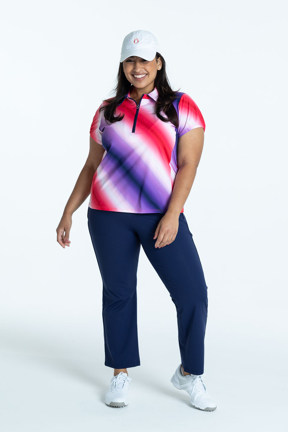 Woman golfer wearing an ombre Prettier Than A Polo shortsleeve golf shirt with navy blue Smooth Your Waist Crop Pant, and a white We've Got You Covered hat