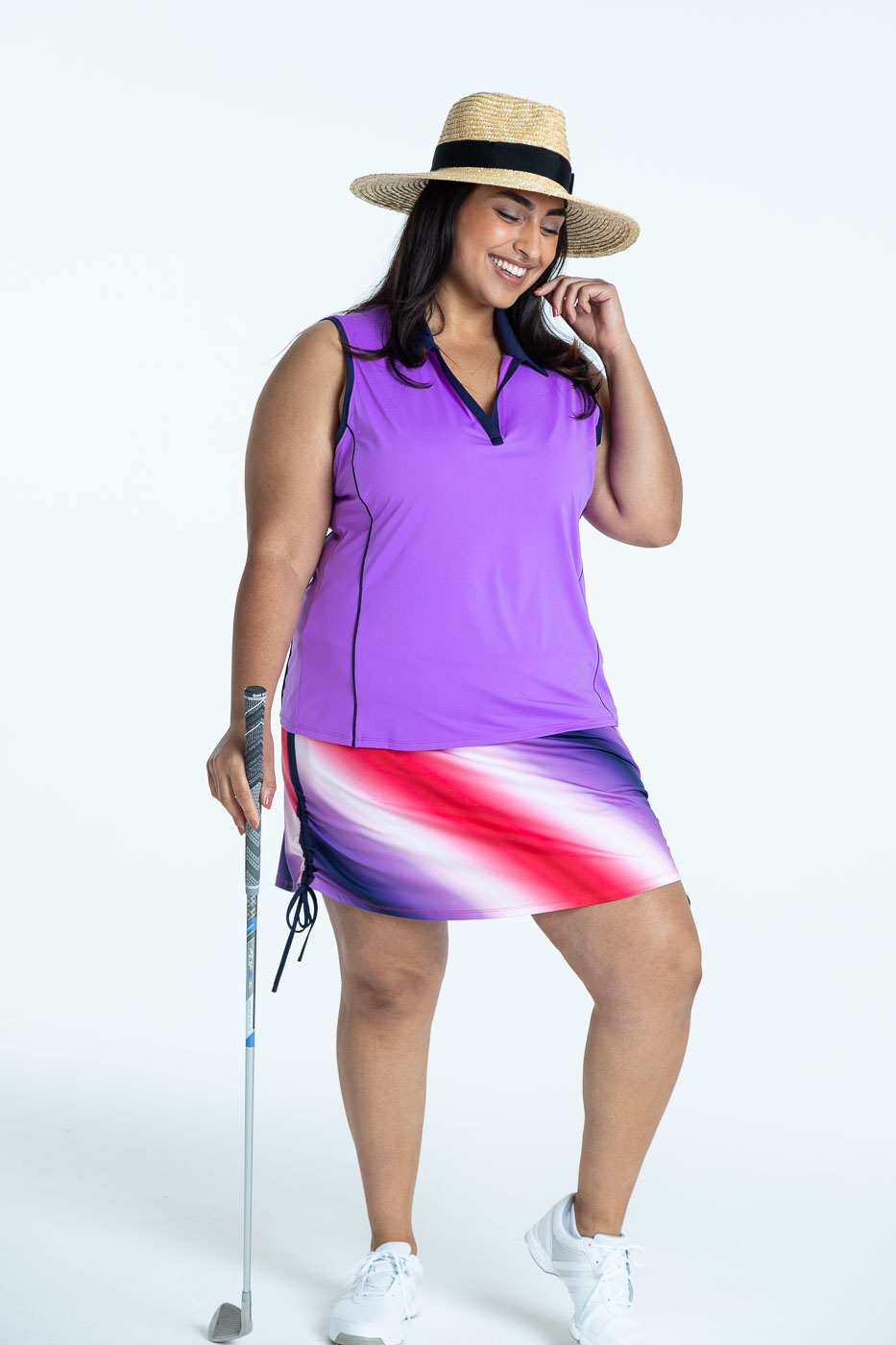 Woman golfer wearing a lilac Waistline Winner sleeveless golf top and a Rouched and Ready ombre print skort