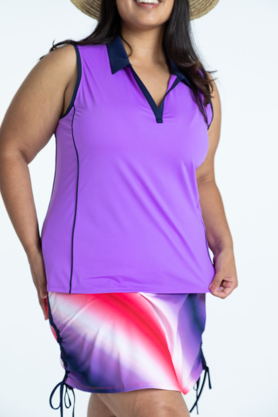 Close up of woman golfer wearing a lilac Waistline Winner sleeveless golf top and a Rouched and Ready ombre print skort