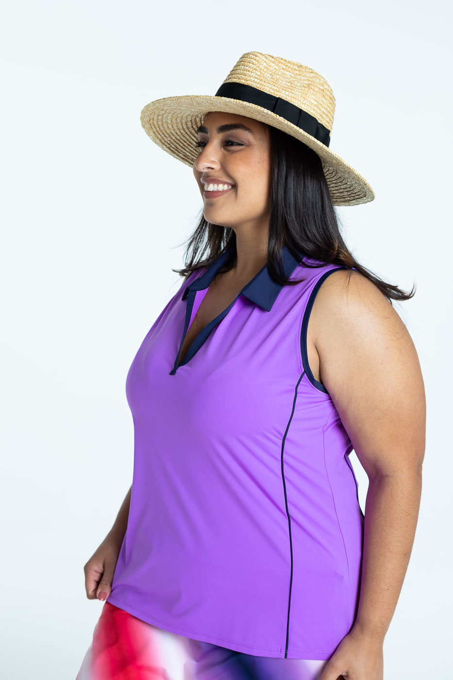 Side view of woman golfer wearing a lilac Waistline Winner sleeveless golf top and a Rouched and Ready ombre print skort