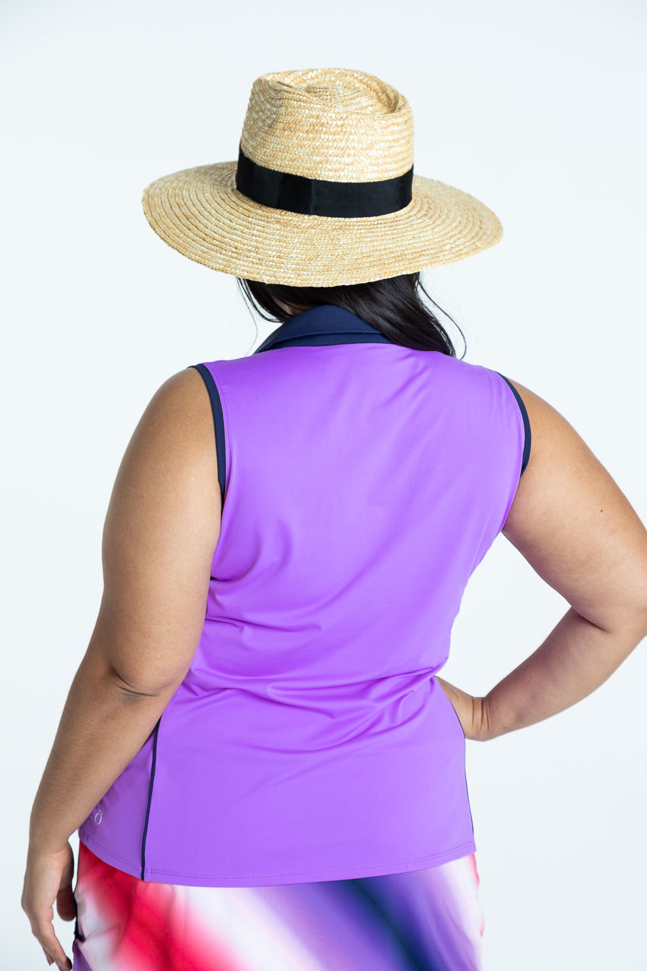 Back view of woman golfer wearing a lilac Waistline Winner sleeveless golf top and a Rouched and Ready ombre print skort