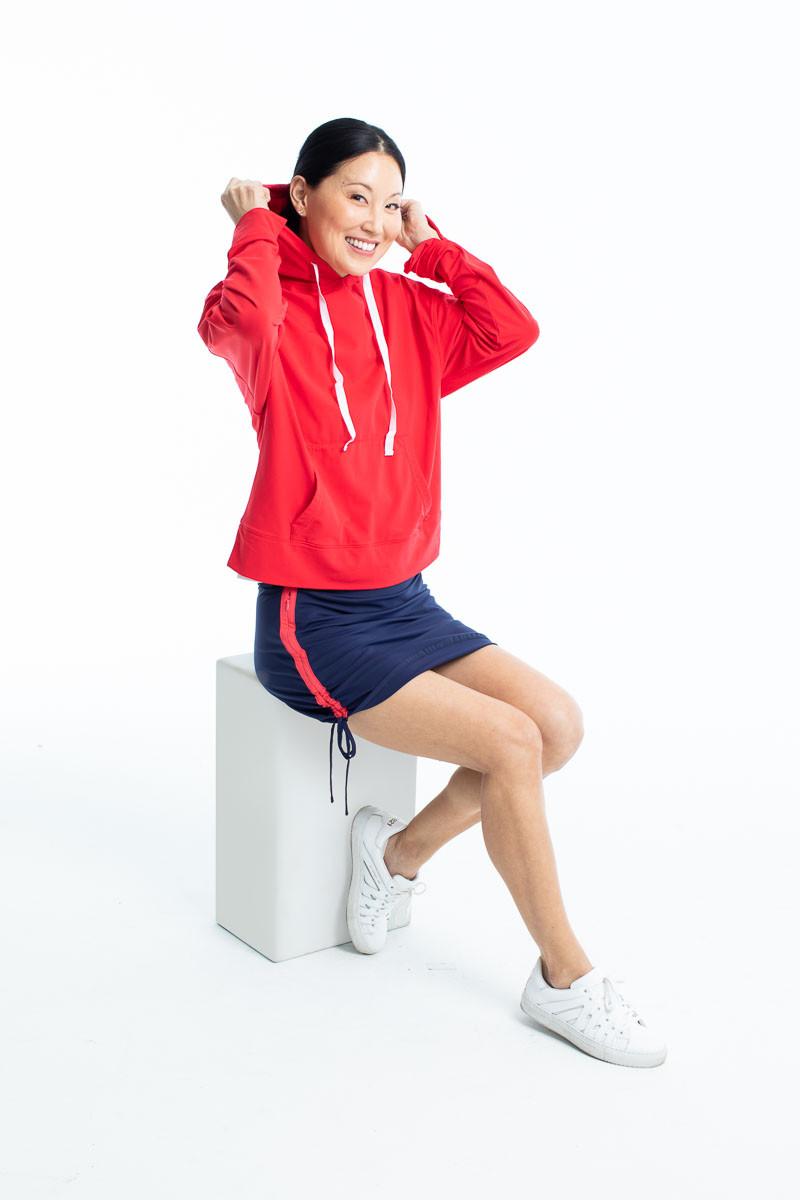 Woman adjusting the hood on her watermelon red Apres 18 longsleeve hoodie