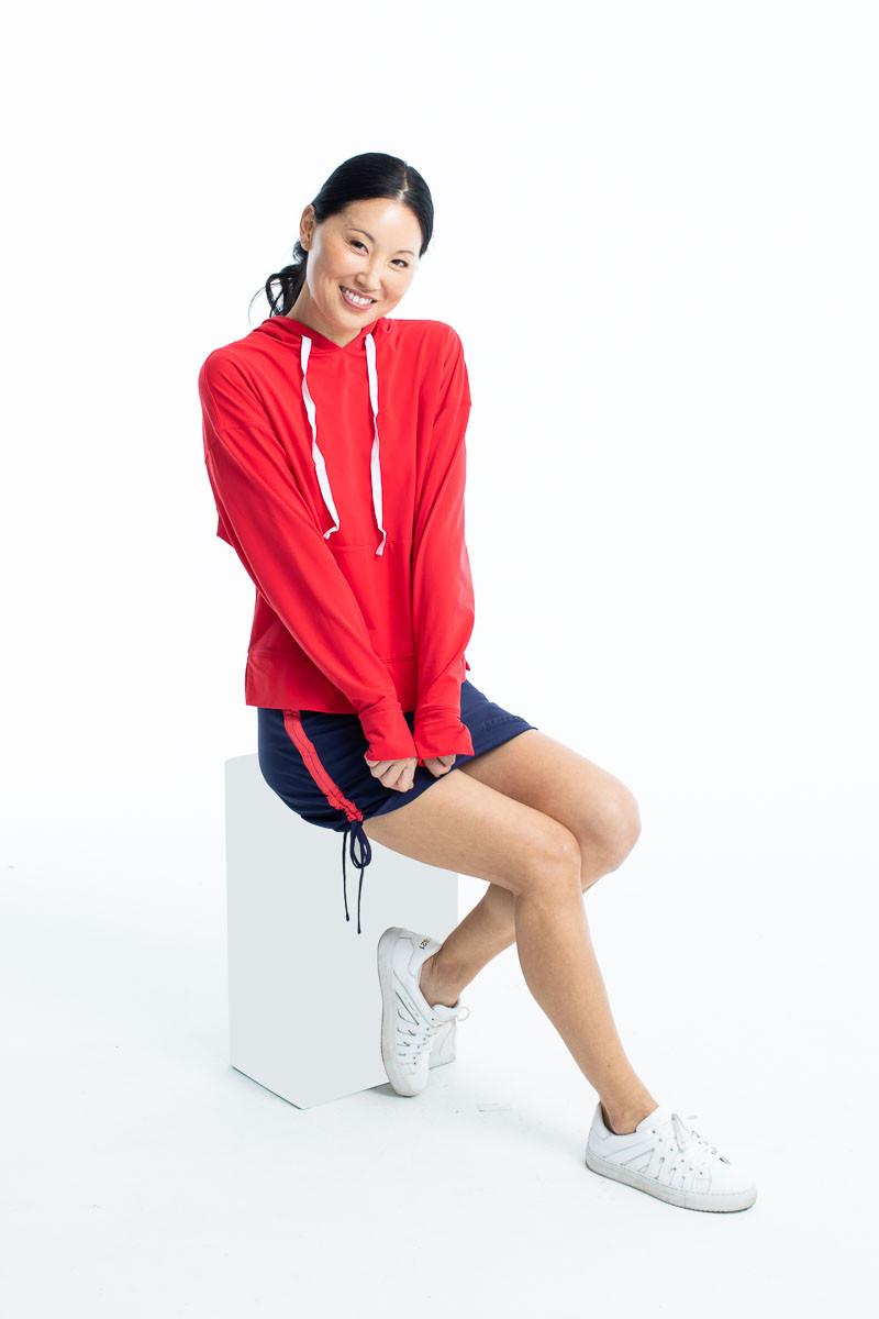 Smiling woman wearing a watermelon red Apres 18 longsleeve hoodie