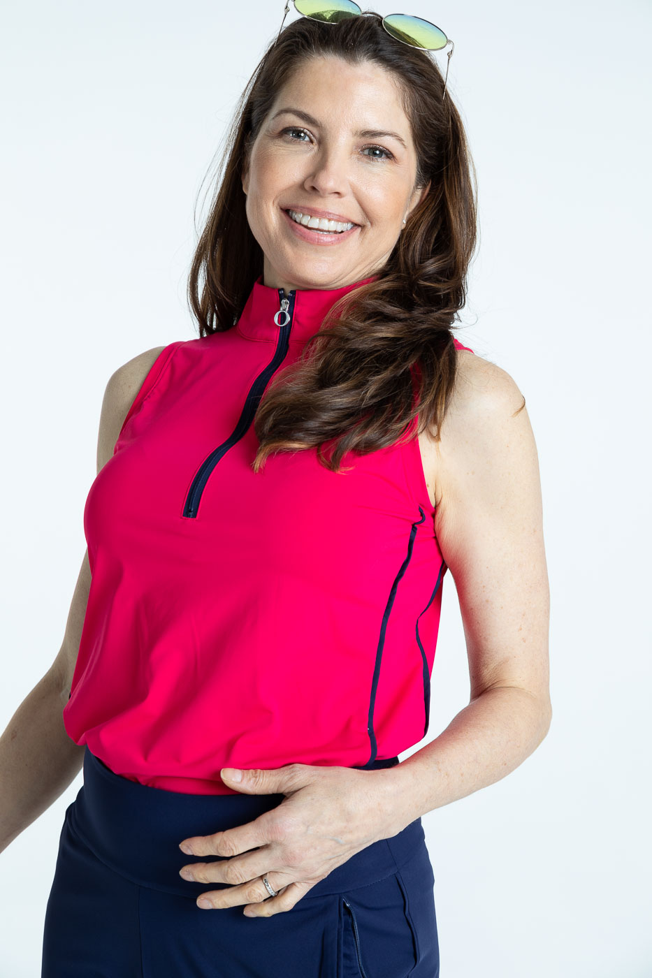 Smiling woman golfer in raspberry red Keep it Covered sleeveless golf top
