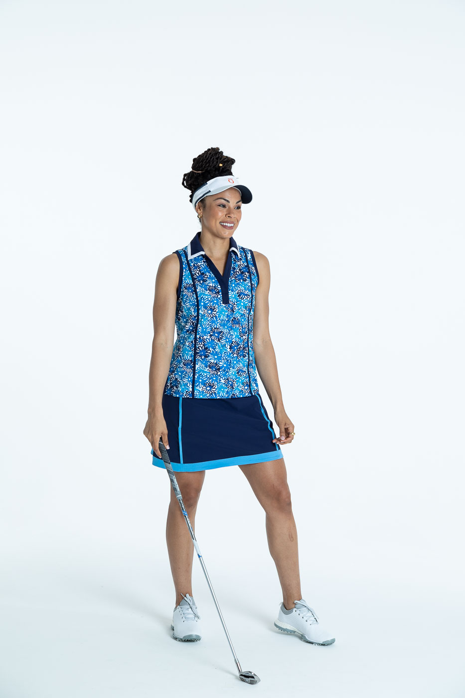Smiling woman golfer in a crazy daisy Shape Shifter sleeveless golf top, a navy blue Fresh and Flirty Golf Skort, and a white No Hat Hair Visor.