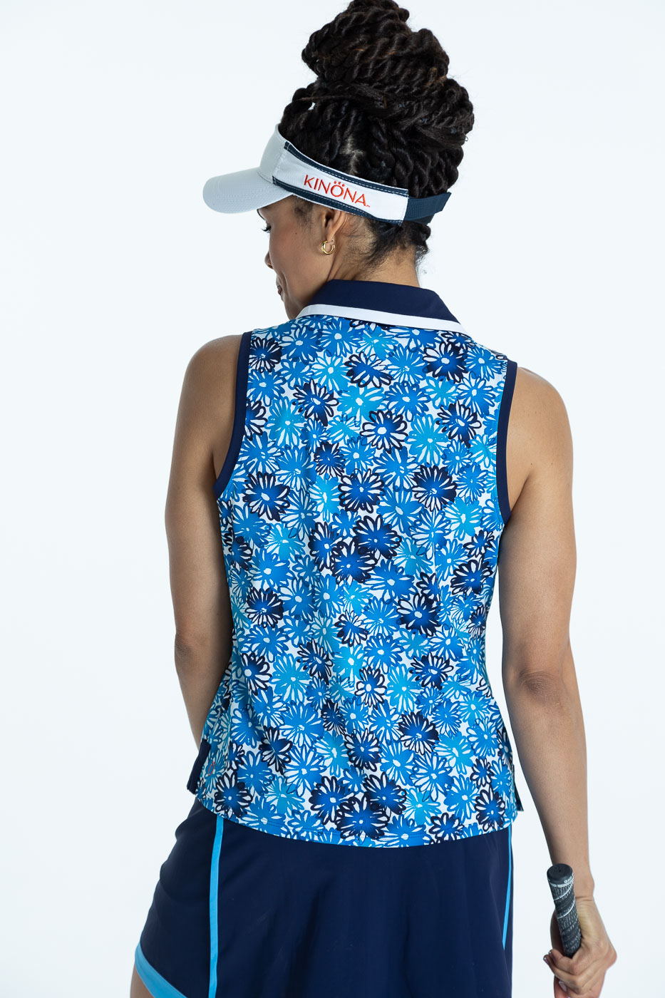 Back view of woman golfer in a crazy daisy Shape Shifter sleeveless golf top, a navy blue Fresh and Flirty Golf Skort, and a white No Hat Hair Visor.