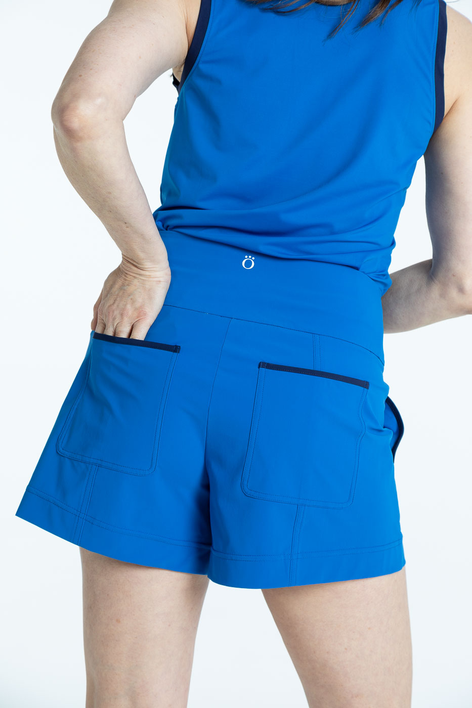Back view of woman golfer in a blueberry blue Shape Shifter sleeveless golf top and blueberry blue Carry My Cargo Shorts
