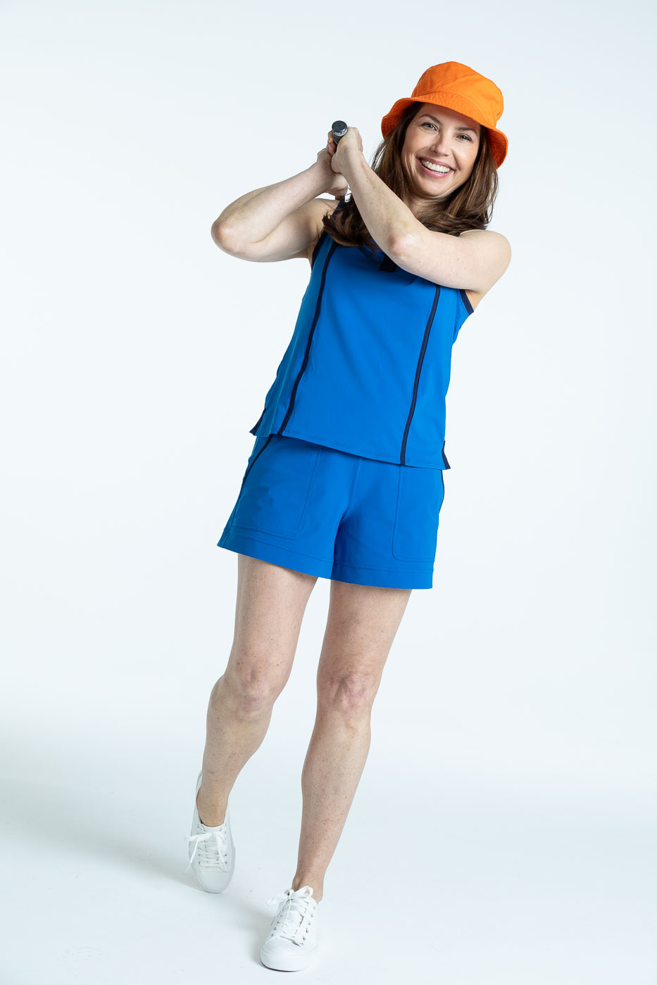 Woman golfer in a blueberry blue Shape Shifter sleeveless golf top and blueberry blue Carry My Cargo Shorts