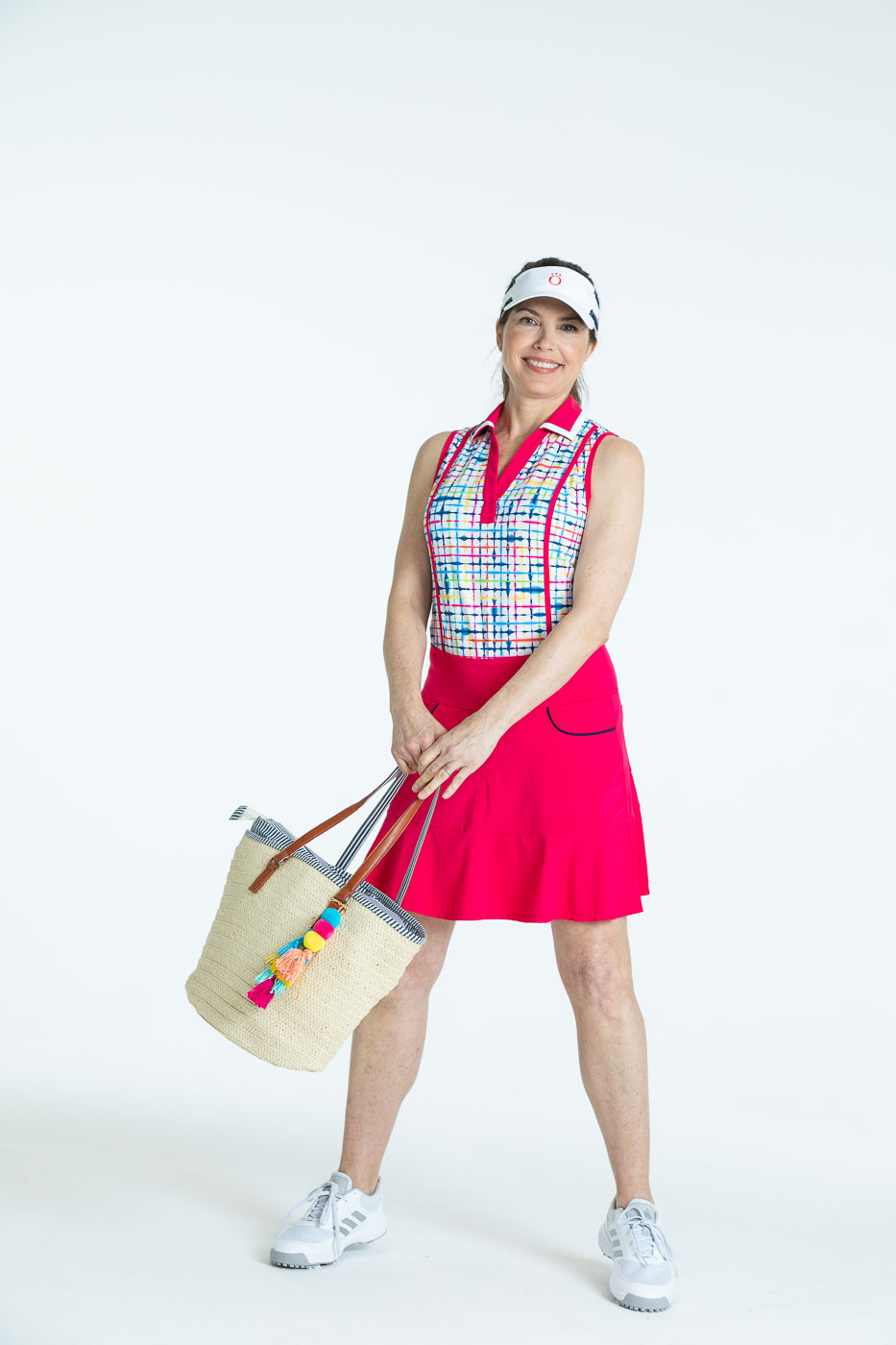 Smiling woman golfer in a blurred lines Shape Shifter sleeveless golf top, a raspberry red Fit and Flare Golf Skort, a white We've Got You Covered Hat, holding a bag.