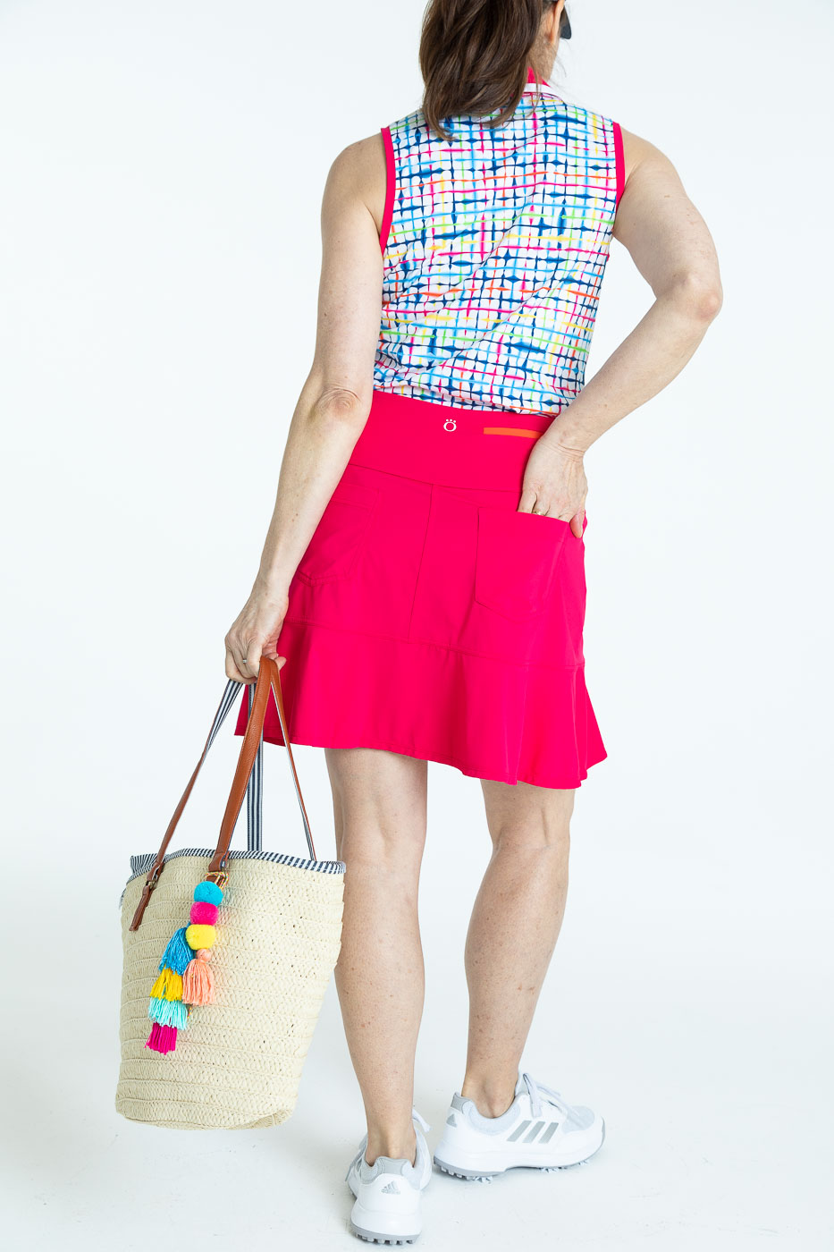 Back view of woman golfer wearing a blurred lines Shape Shifter sleeveless golf top and a raspberry red Fit and Flare Golf Skort holding a bag.