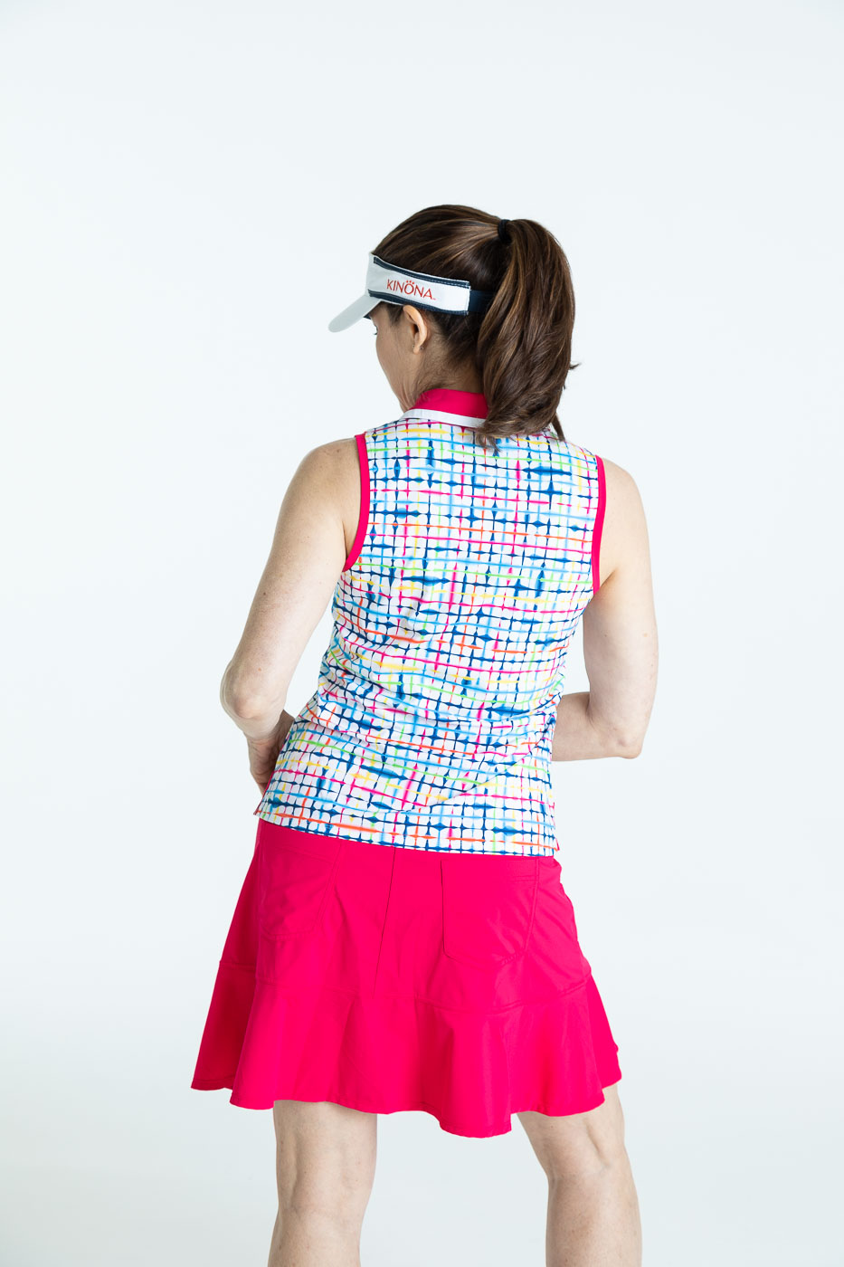 Back view of woman golfer wearing a blurred lines Shape Shifter sleeveless golf top, a raspberry red Fit and Flare Golf Skort, and a white No Hat Hair Visor.