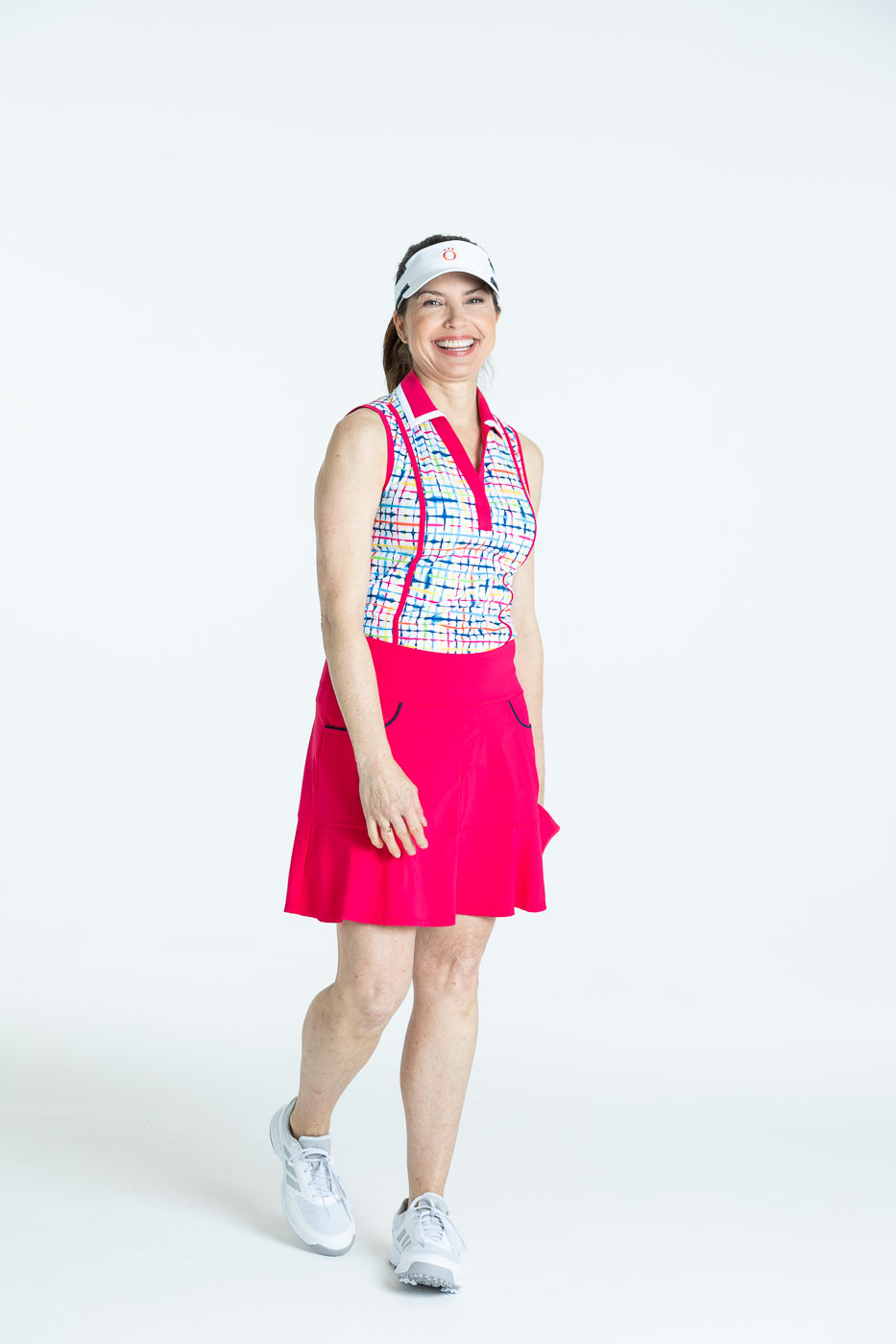 Smiling woman golfer in a blurred lines Shape Shifter sleeveless golf top, a raspberry red Fit and Flare Golf Skort, and a white We've Got You Covered Hat.