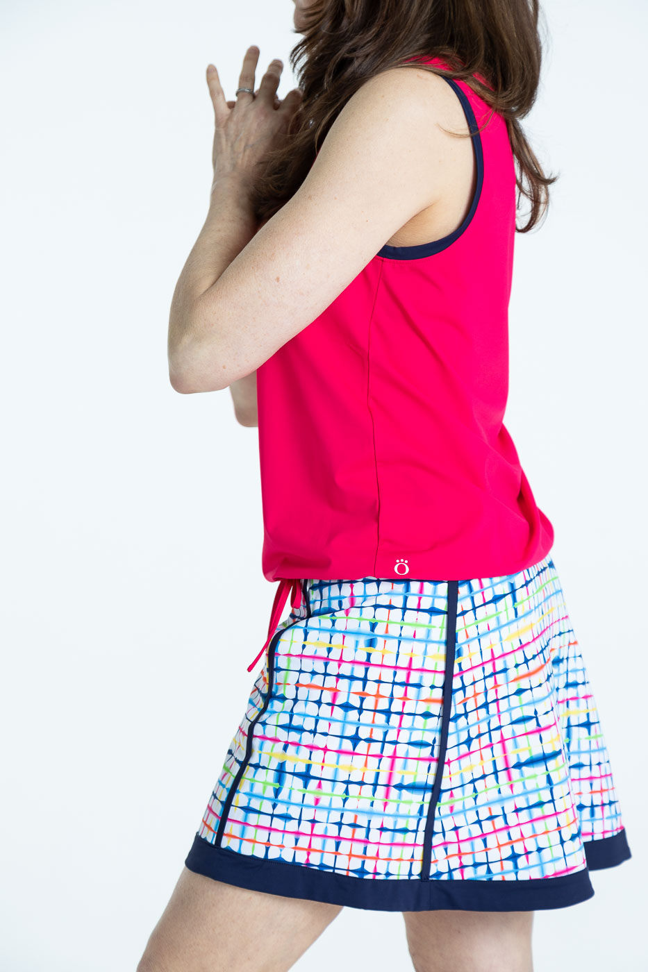 Side view of woman golfer in raspberry red Free and Easy Sleeveless Golf Shirt and a blurred lines Fresh and Flirty Golf Skort