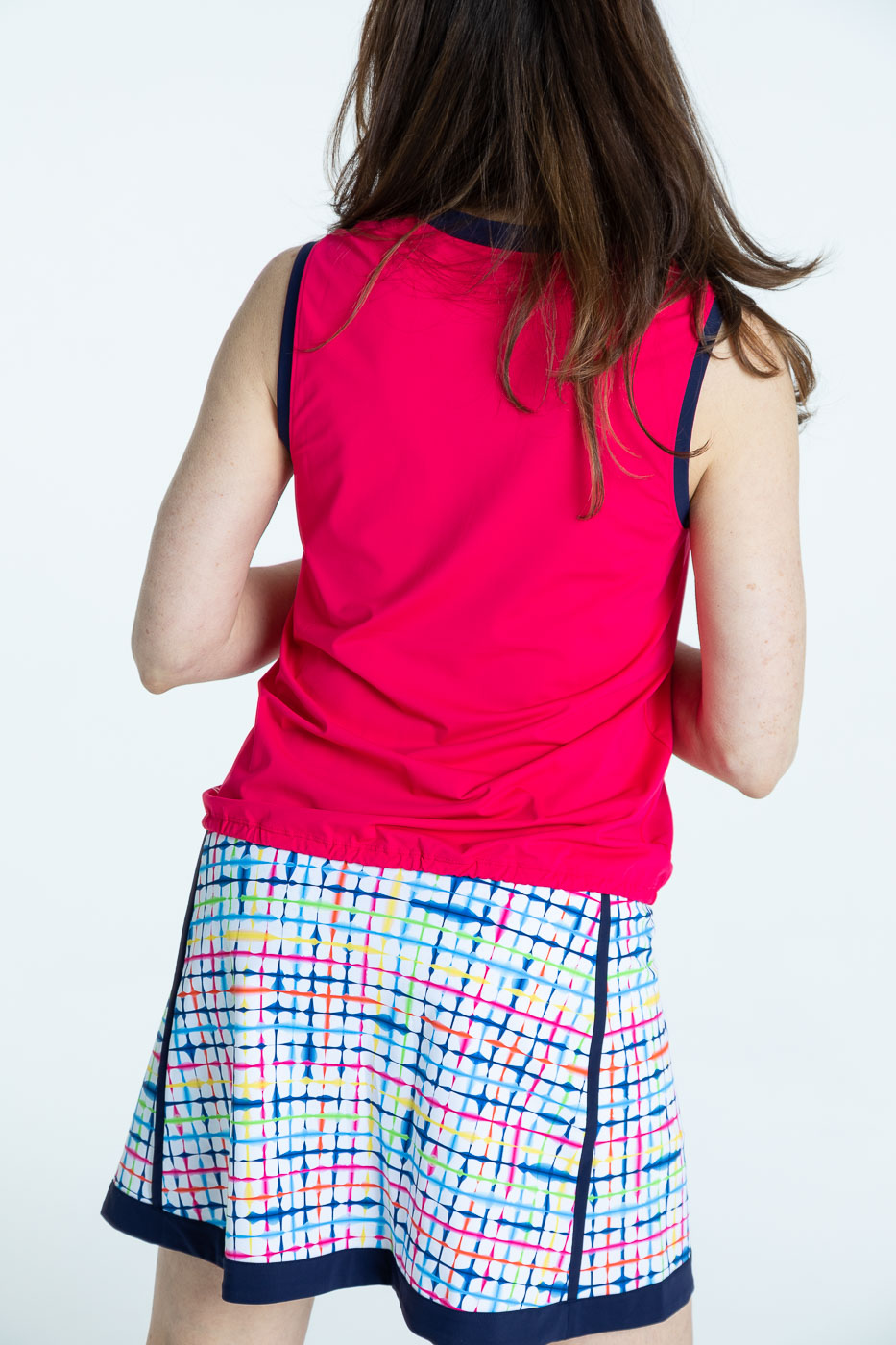 Back view of woman golfer in raspberry red Free and Easy Sleeveless Golf Shirt and a blurred lines Fresh and Flirty Golf Skort