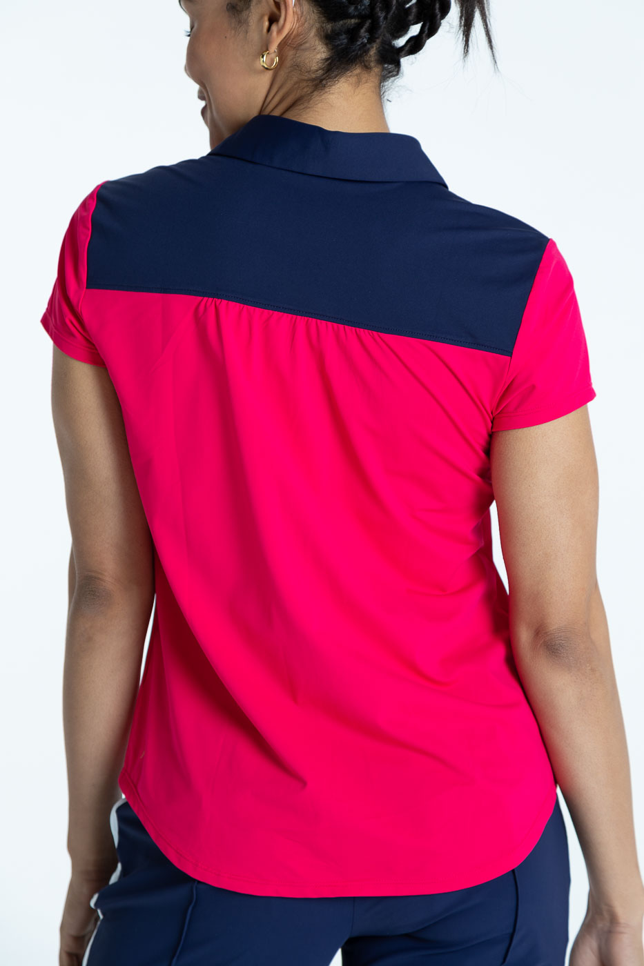 Back view of golfer in a raspberry red Shoulder Opener Shortsleeve golf shirt