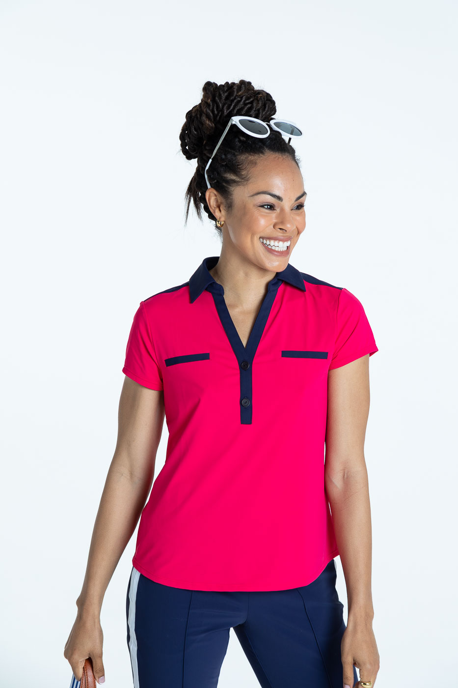 Woman golfer in a raspberry red Shoulder Opener Shortsleeve golf shirt and  navy blue Tailred Track Golf Pant.