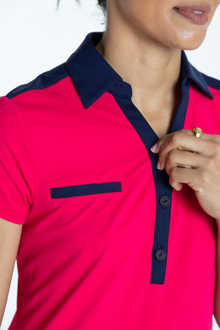 Close front view of woman golfer in a raspberry red Shoulder Opener Shortsleeve golf shirt
