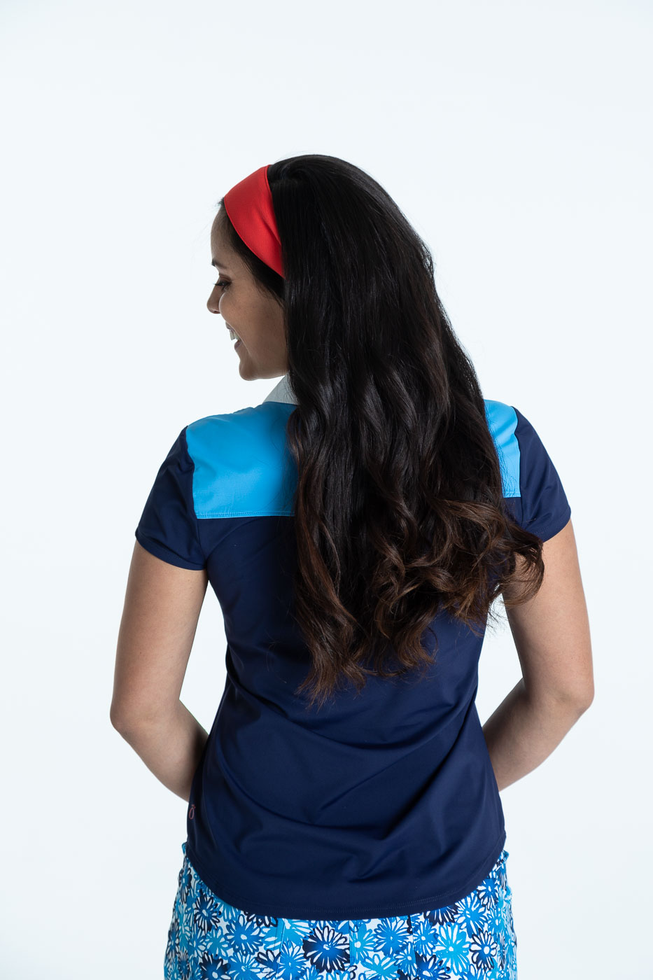 Back view of woman golfer in navy blue Shoulder Opener Shortsleeve Golf Top and crazy daisy Fit and Flare Golf Skort.