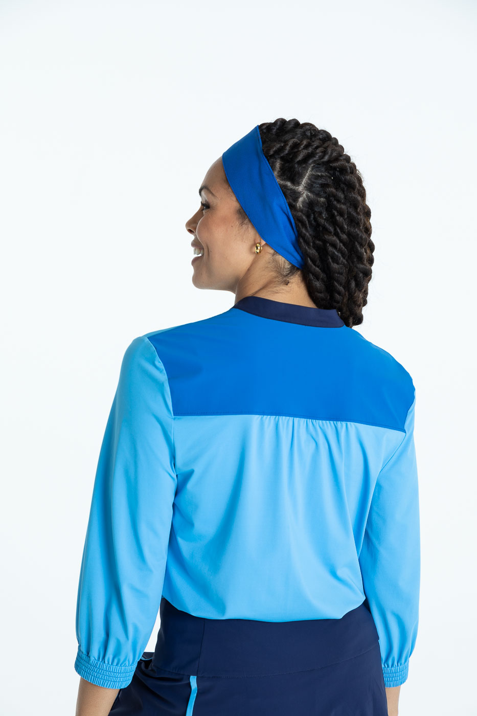 Back view of woman wearing a cornflower blue Swing Easy 3/4 Sleeve golf shirt