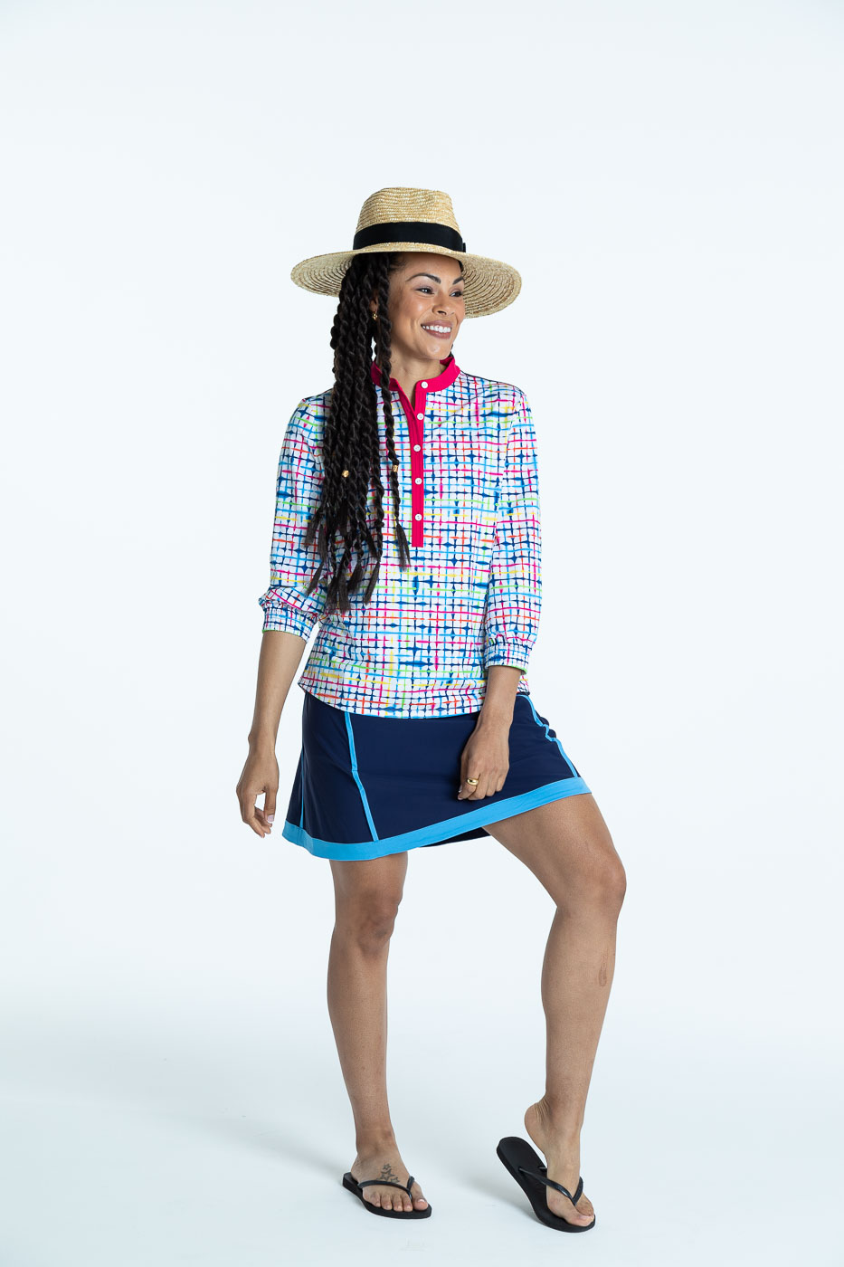 Smiling woman wearing a blurred lines Swing Easy 3/4 Sleeve golf shirt and a navy blue Fresh and Flirty golf skort