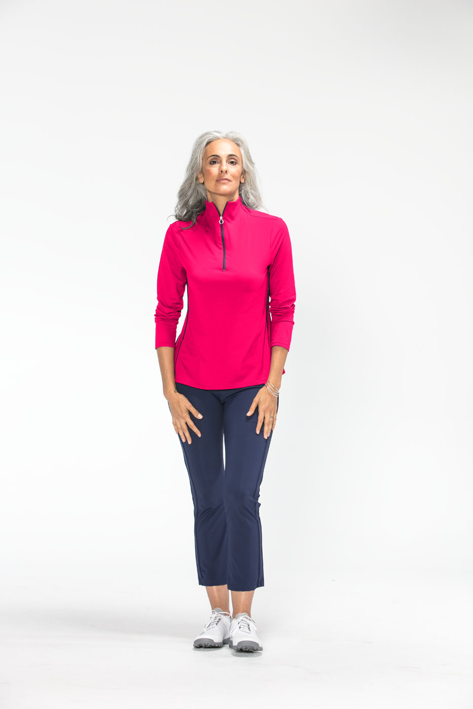 Woman golfer wearing a raspberry red Keep It Covered longsleeve golf top and navy blue Smooth Your Waist golf crop pants.