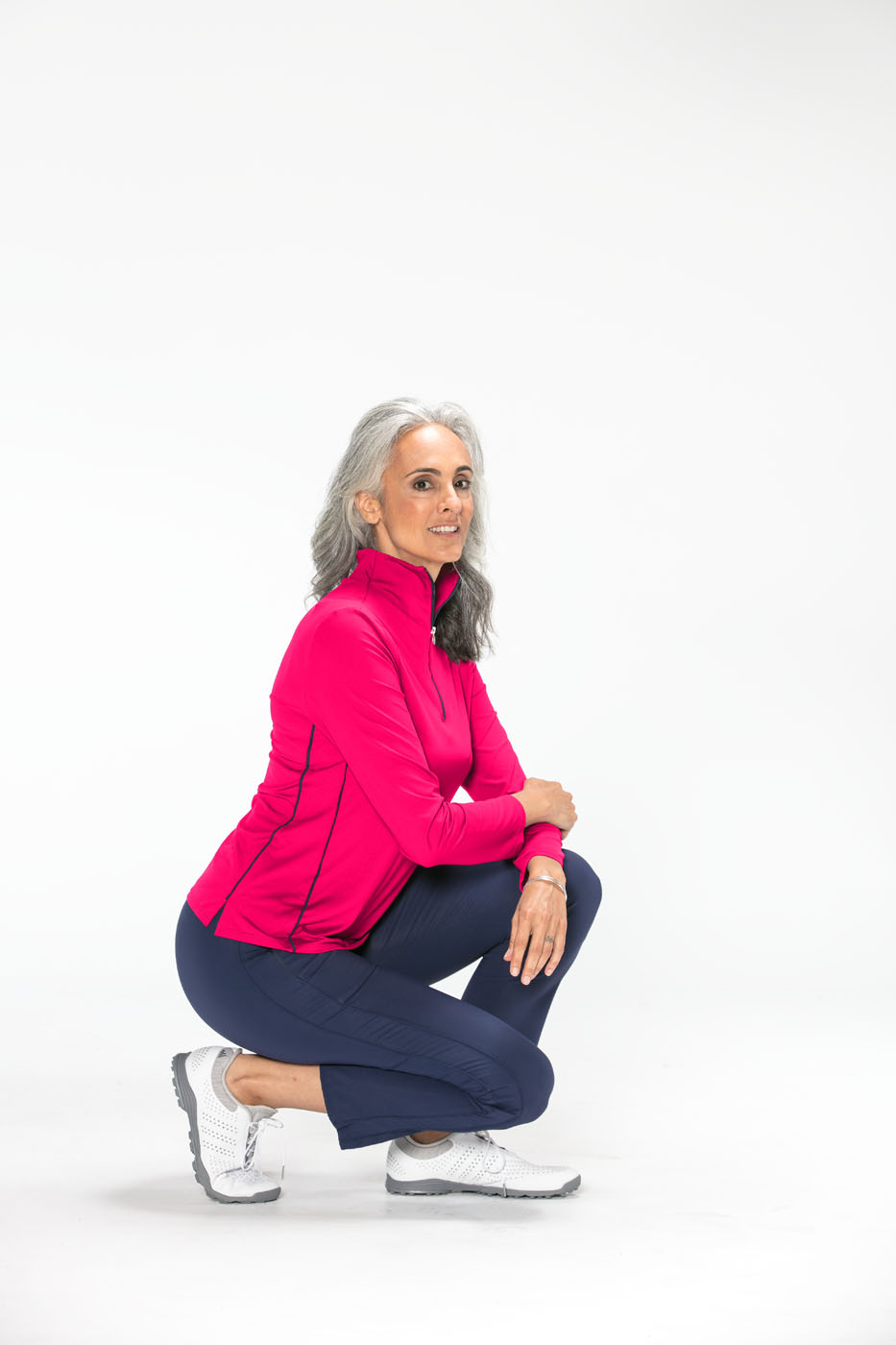 Woman crouching wearing a raspberry red Keep It Covered longsleeve golf top and navy blue Smooth Your Waist golf crop pants.