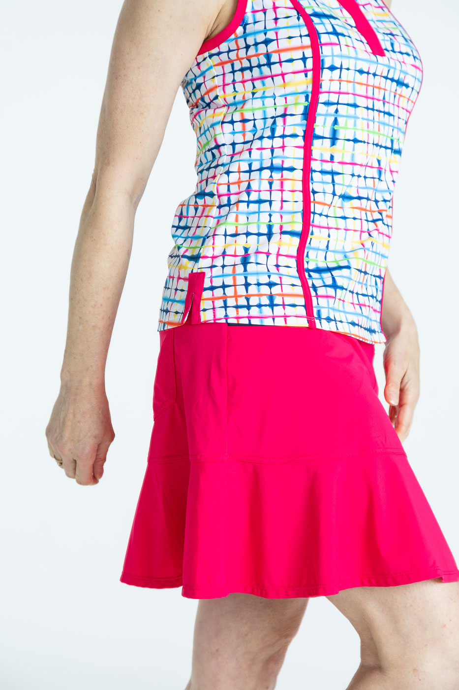 Side view of woman golfer wearing a raspberry red Fit and Flare golf skort and a blurred lines Shape Shifter sleeveless golf top