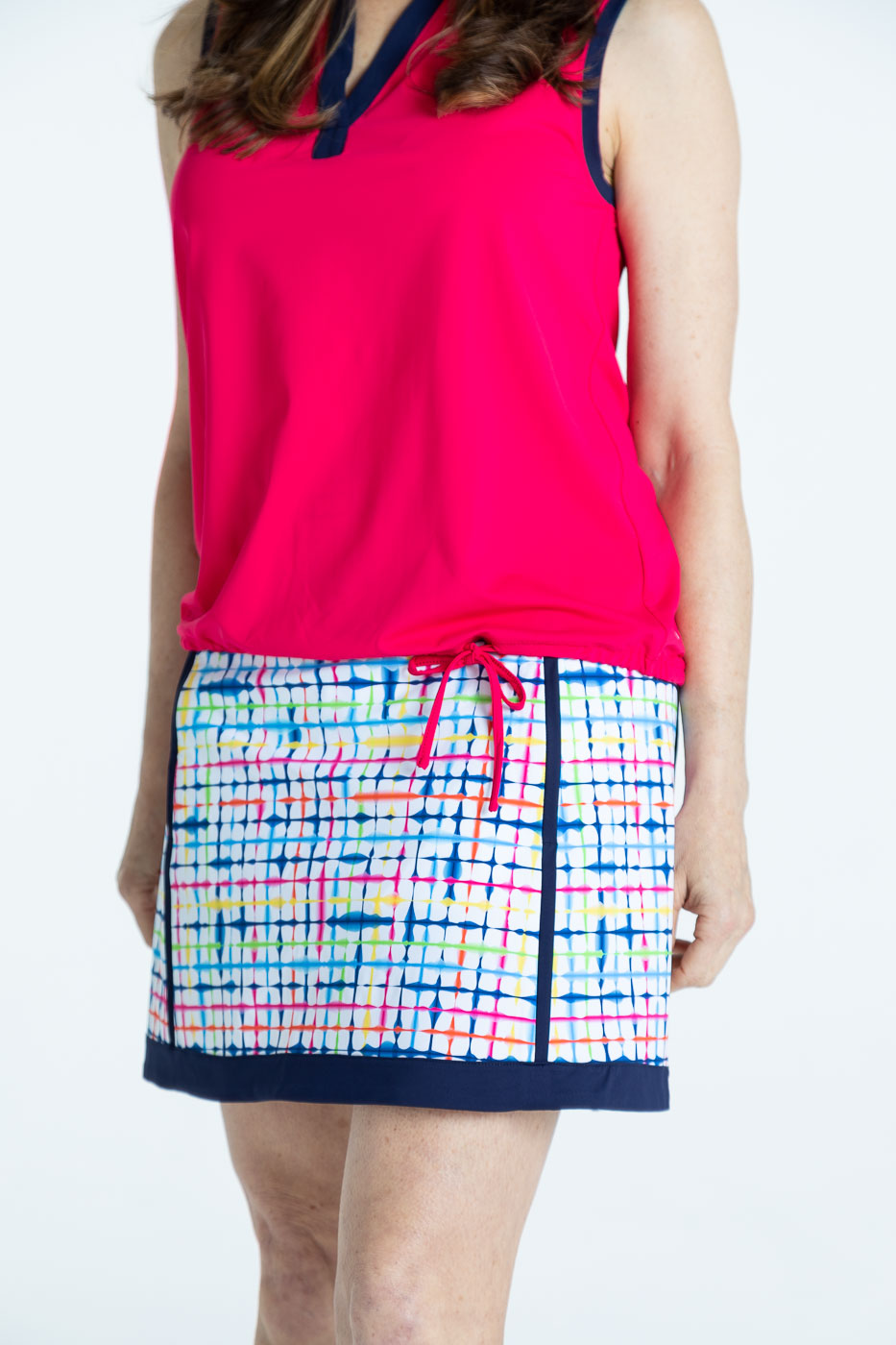 Closer front view of woman wearing a blurred lines Fresh and Flirty golf skort with a raspberry red Free and Easy sleeveless golf shirt